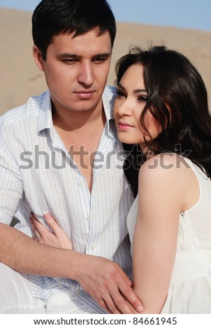 Young couple in love in a white dress sitting on sand