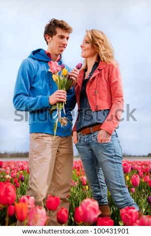 Young couple in love in Dutch flower fields - stock photo