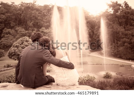 Young couple in love in the park on fountain background in vintage color tone