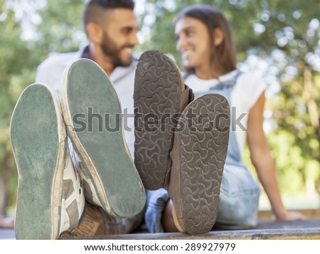 young couple in love in the park with his feet foreground - stock photo