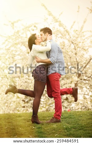 young couple in love kissing in park - stock photo