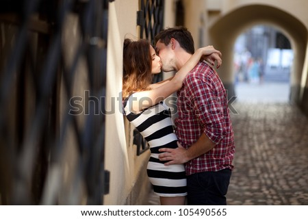 Young couple in love, kissing in the old part of town - stock photo