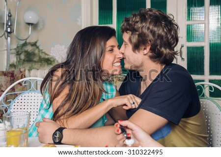 Young couple in love laughing and embracing at home breakfast with friends - stock photo