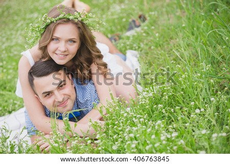 Young couple in love laying on the flower meadow