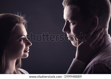 Young couple in love looking at each other on a black background