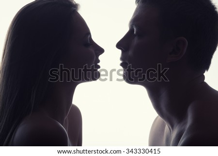 Young couple in love looking at each other on a white background - stock photo