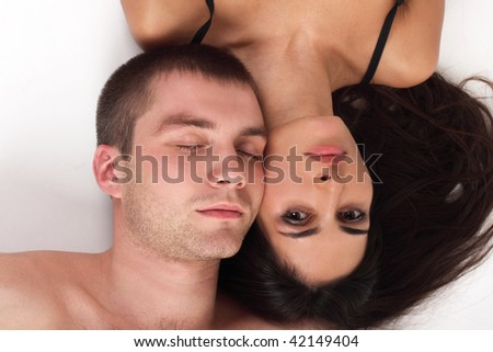 Young couple in love lying down in white background (man closed his eyes)