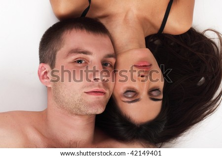 Young couple in love lying down in white background (woman covered her eyes) - stock photo