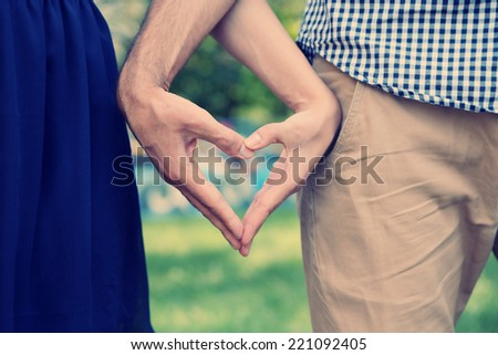 Young couple in love make heart - stock photo