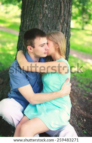 Young couple in love, man and woman resting near tree sitting in the park together, warm feelings - stock photo