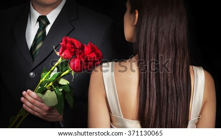 Young couple in love. Man gives his girlfriend red roses. - stock photo
