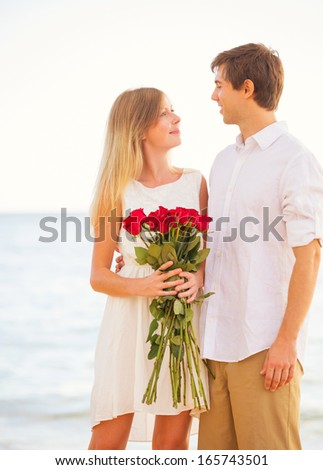 Young couple in love man giving beautiful woman bouquet - Boy propose girl with rose image ...