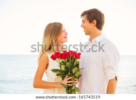 Young Couple in Love, Man giving beautiful woman bouquet of red roses, Romantic Date - stock photo