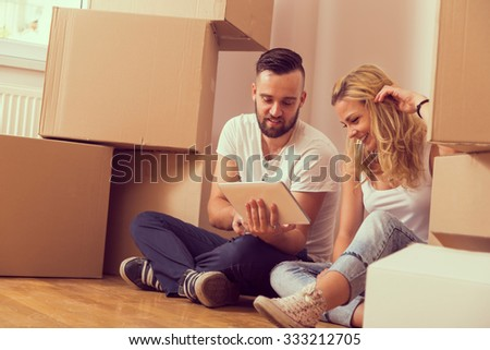 Young couple in love moving in a new apartment, sitting on the floor, planning to redecorate their new home - stock photo