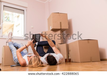 Young couple in love moving in a new flat, lying on the floor and surfing the web on a tablet computer in search of new redecoration ideas