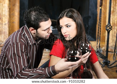 Young couple in love near fireplace drinking wine - stock photo