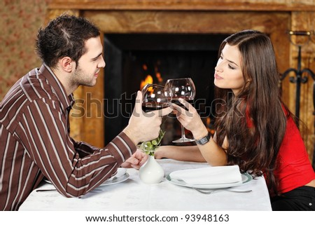 Young couple in love near fireplace, holding glasses of wine and cheers - stock photo