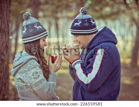 Young couple in love outdoor drinking hot tea. toned image - stock photo