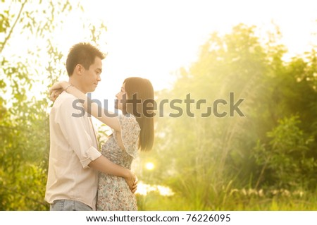 Young couple in love, outdoor in sunset - stock photo