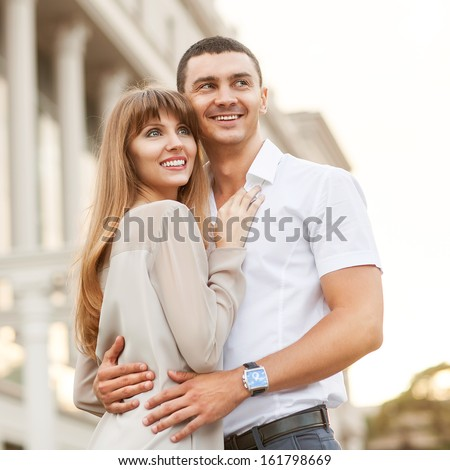 Young couple in love outdoor. She pressed against him, he is a gentle hugs her.