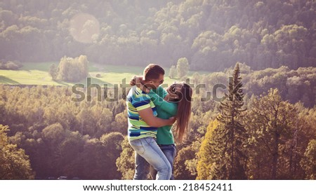 Young couple in love outdoor, smiling and looking at each other. - stock photo