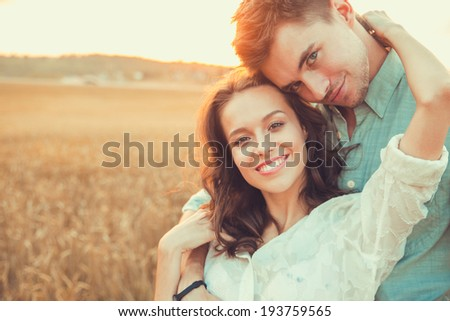 Young couple in love outdoor.Stunning sensual outdoor portrait of young stylish fashion couple posing in summer in field.Soft sunny colors.