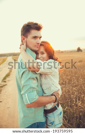 Young couple in love outdoor.Stunning sensual outdoor portrait of young stylish fashion couple posing in summer in field.Soft sunny colors.  - stock photo