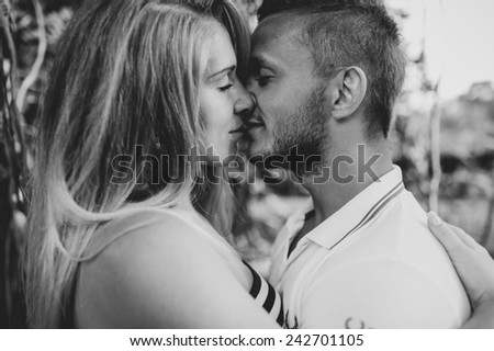 Young couple in love outdoor.Stunning sensual outdoor portrait of young stylish fashion couple posing in summer - stock photo