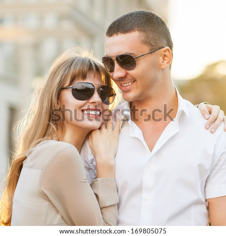 Young couple in love outdoor. They are smiling and looking at each other. - stock photo