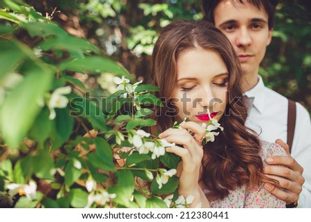Young couple in love outdoor. They are smiling and looking at each other.Happy Smiling Couple in love.Stunning sensual outdoor portrait of young stylish fashion couple posing in summer in park - stock photo