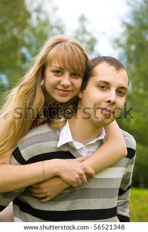 Young couple in love outdoors against summer park - stock photo