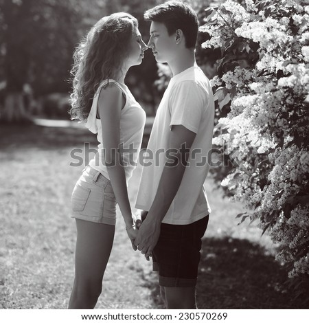 Young couple in love outdoors, moment kiss  - stock photo