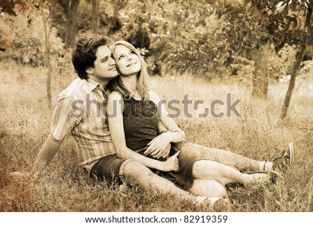 Young couple in love outdoors. Photo in old image style. - stock photo