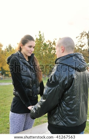 Young couple in love outdoors - woman and man holding their hands