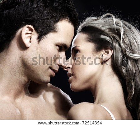Young couple in love. Over dark  background - stock photo