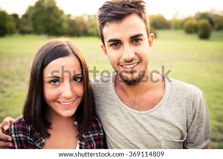 Young couple in love portrait at the park - stock photo