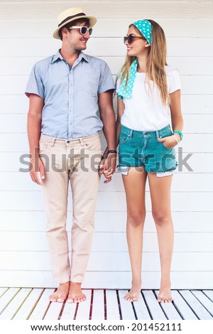 Young couple in love posing near white beach cafe in summer retro bright outfits, holding hands looking to each other and smiling. - stock photo