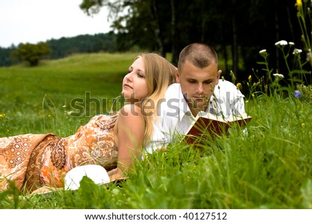 young couple in love relaxing on the summer meadow - stock photo