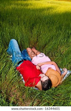 young couple in love resting in a field, summer day - stock photo