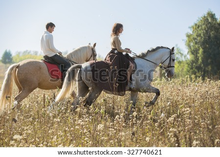 Young couple in love riding a horse - stock photo