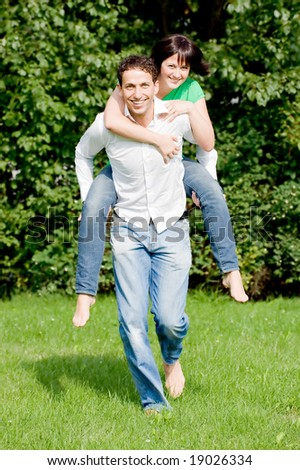 Young couple in love running over a green - stock photo