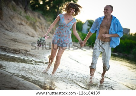 young couple in love running through the water holding hands - stock photo