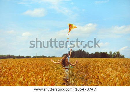 Young couple in love running with a kite in a yellow box - stock photo