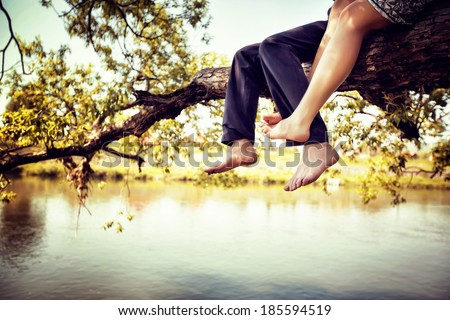 Young couple in love sitting cross-legged on a tree branch above the river in nice sunny day. Photo is colorized in warm tints. - stock photo