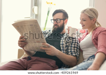 Young couple in love sitting on a couch in their apartment next to the window, enjoying their free time, reading newspaper and drinking coffee. Lens flare effect on window - stock photo