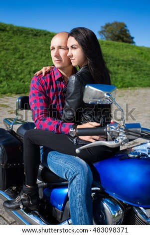 young couple in love sitting on blue retro motorbike