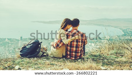 Young couple in love sitting on hill above the city. Concept of tranquil life from the urban bustle. Image with instagram filter - stock photo
