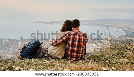 Young couple in love sitting on hill and looking at the city, rear view. Concept of tranquil life from the urban bustle - stock photo