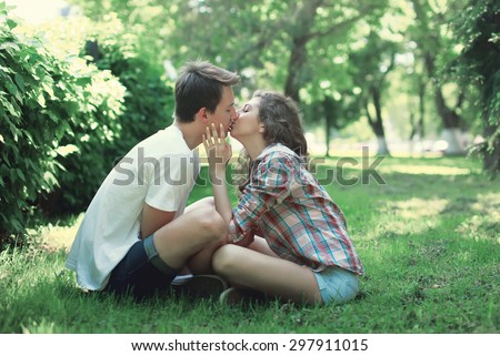Young couple in love sitting on the grass and kissing  - stock photo