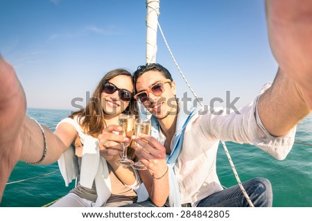 Young couple in love taking selfie on sailing boat cheering with champagne wine - Happy jubilee party cruise travel on luxury sailboat with boyfriend and girlfriend - Bright sunny afternoon color tone - stock photo